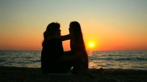 stock-footage-sunrise-mother-with-daughter-are-sitting-on-a-beach-together-dolly